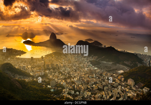Rio de Janeiro cityscape, Brazil. Sugar Loaf, Botafogo beach and neighborhood seen from Corcovado at sunrise impressive - Stock Image
