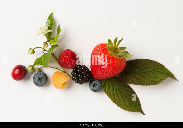 Mixture of berries: strawberry, red and golden raspberries, blackberry, blueberry and cranberry with leaves and - Stock Image