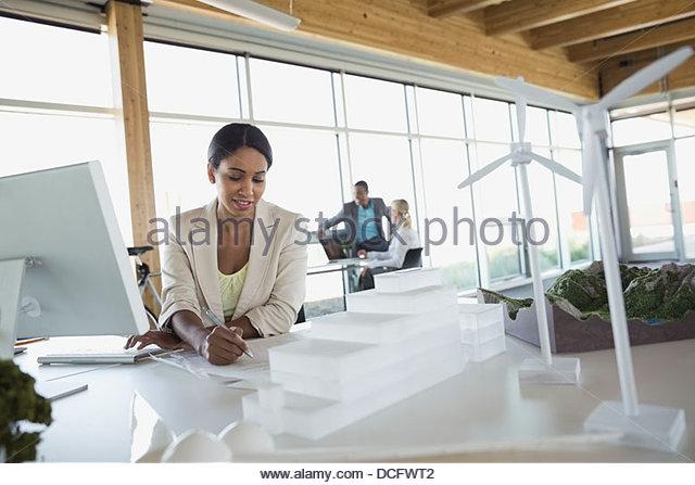 Sustainable energy engineer working on prototypes and blueprints - Stock Image