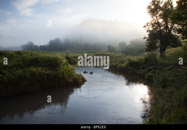 A foggy field with a beautiful creek - Stock Image