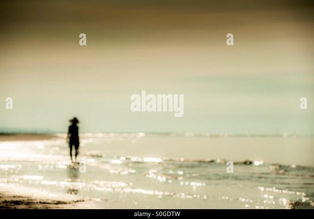 A figure of woman by the sea alone - Stock Image