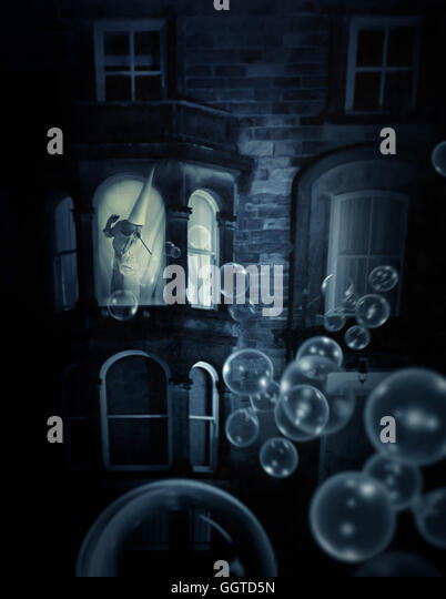 woman wearing cone hat standing in window making bubbles surreal conceptual - Stock Image
