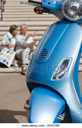 Senior couple sitting on urban steps with street map man pointing focus on blue motor scooter parked in foreground - Stock Image