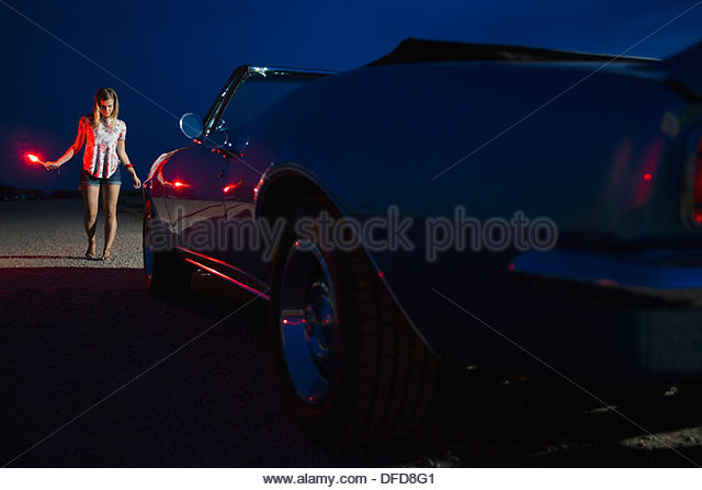 Young woman holding roadside flare near convertible - Stock Image