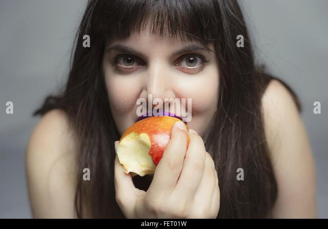 Portrait Of Young Woman Eating Apple - Stock Image