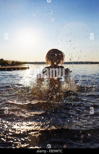 Sweden, Vastra Gotaland, Skagern, Girl (6-7) splashing in lake at sunset - Stock Image