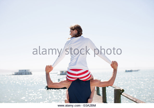 Man carrying wife on shoulders on pier at ocean - Stock-Bilder