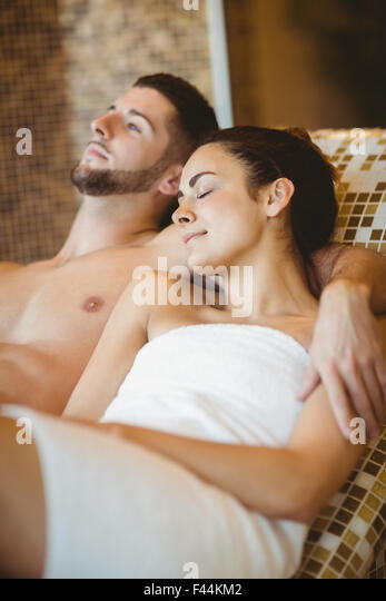 Happy couple lying down together - Stock Image