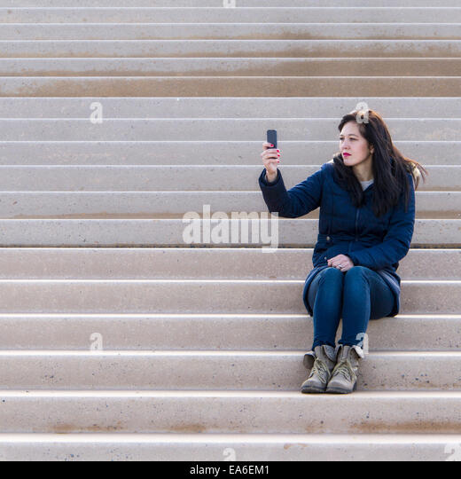 Woman sitting on a step taking a selfie - Stock Image