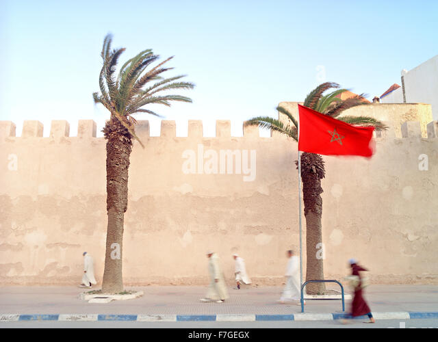 Moroccan muslim men walk briskly past the city walls on his way to morning prayers. - Stock Image