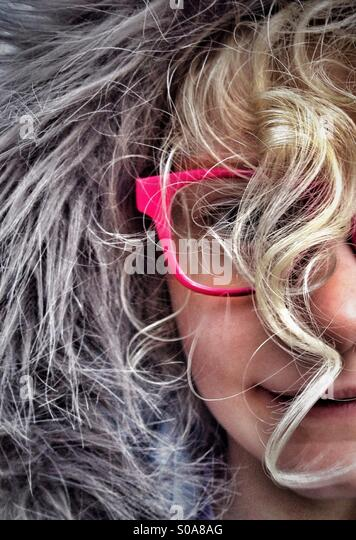 Young girl wearing furry hood and red glasses with face obscured by curly blond hair - Stock Image