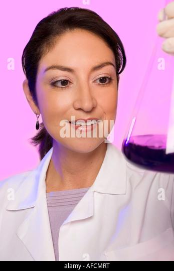 Science researcher checks fluid in beaker. - Stock Image