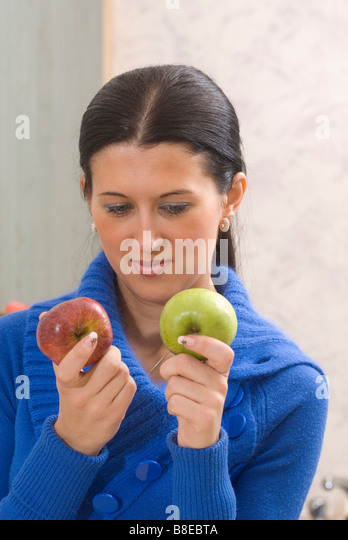 Woman choosing between green and red apples - Stock Image
