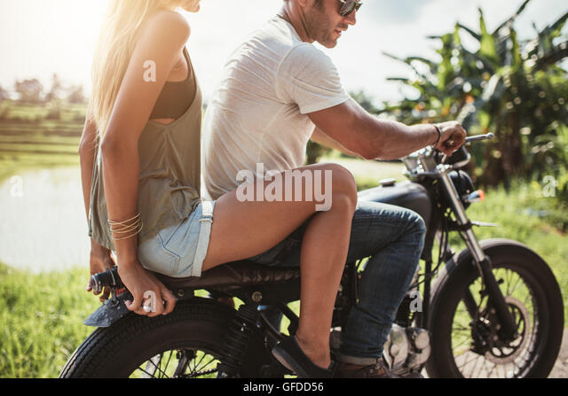 Cropped shot of young man riding on a motorcycle with girlfriend on country road. Man and woman riding on a motorcycle. - Stock Image
