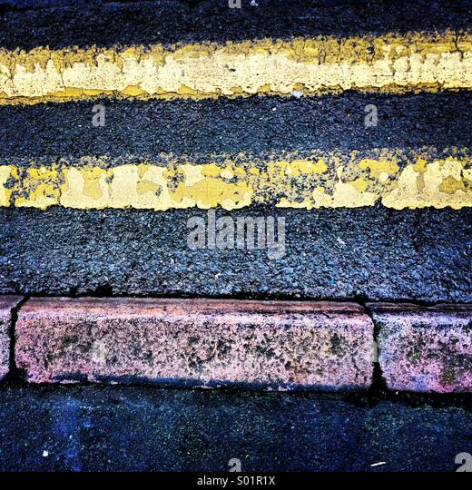 Double Yellow Lines and Pavement Kerb. - Stock Image