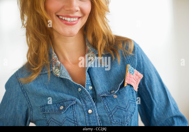 Woman wearing denim jacket with US flag in pocket, studio shot - Stock Image