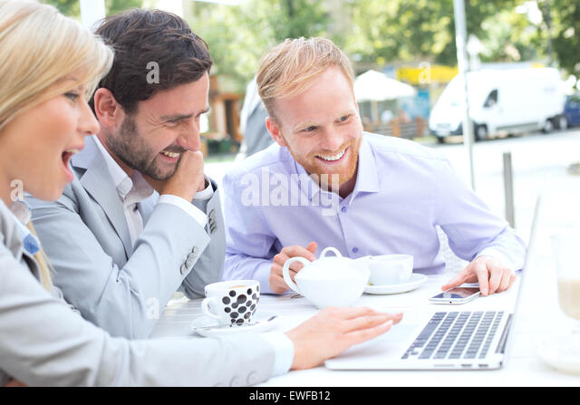 Cheerful businesspeople using laptop together at sidewalk cafe - Stock Image