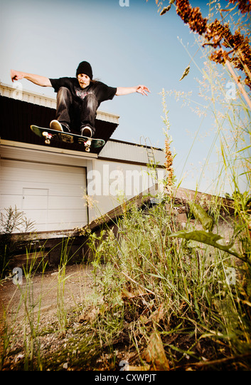 Man skating on grassy concrete - Stock Image