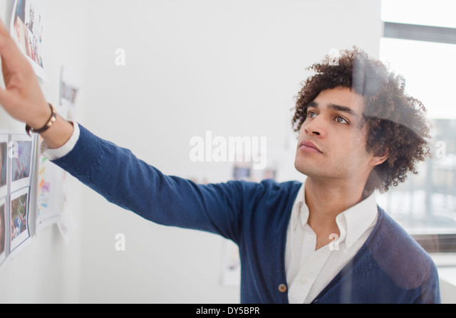 Young man looking at images on wall - Stock Image