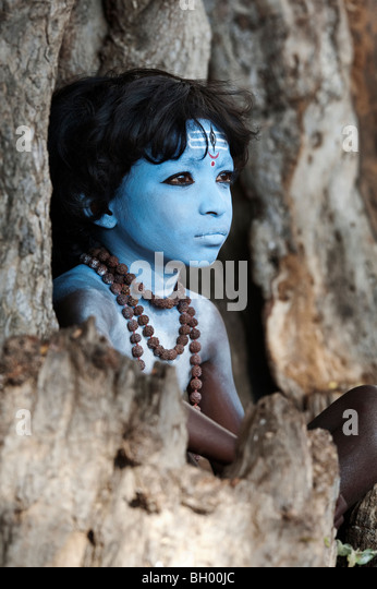 Indian boy, face painted as the Hindu god Shiva sitting in an old tree stump - Stock-Bilder