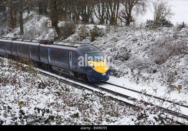 A train rushing through the snowy kent winter countryside - Stock Image