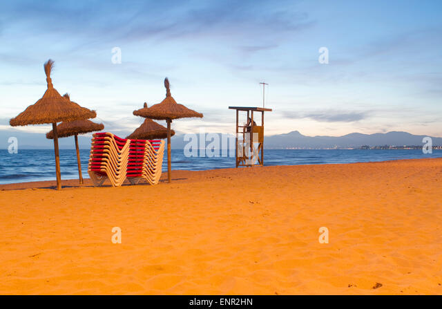 Wicker umbrellas at the beach at sunset, Porto Colon, Travel to Mallorca - Stock Image