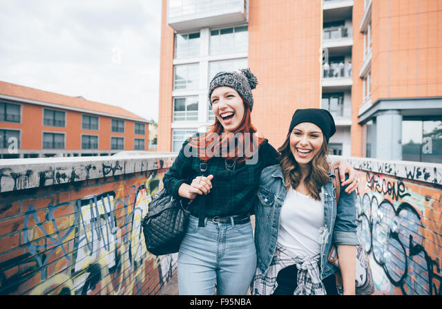 Knee figure of two young handsome caucasian blonde and redhead straight hair women walking hugging outdoor in the - Stock Image