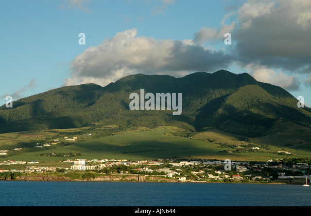 St Kitts Caribbean coast with green mountains behind scenic shoreline - Stock Image