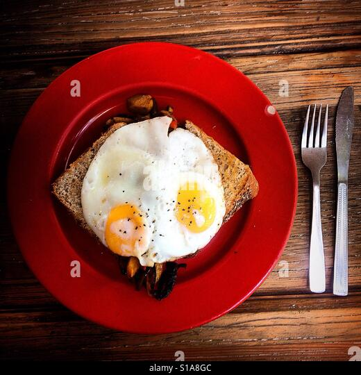 Two eggs on top of wholemeal bread in a red plate by a fork and a knife in Pan Comido restaurant in Mexico City, - Stock-Bilder