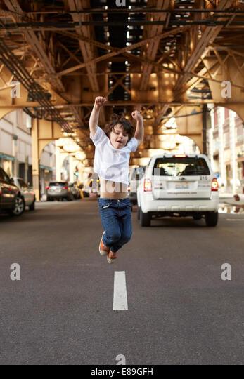 Boy jumping in the street - Stock-Bilder