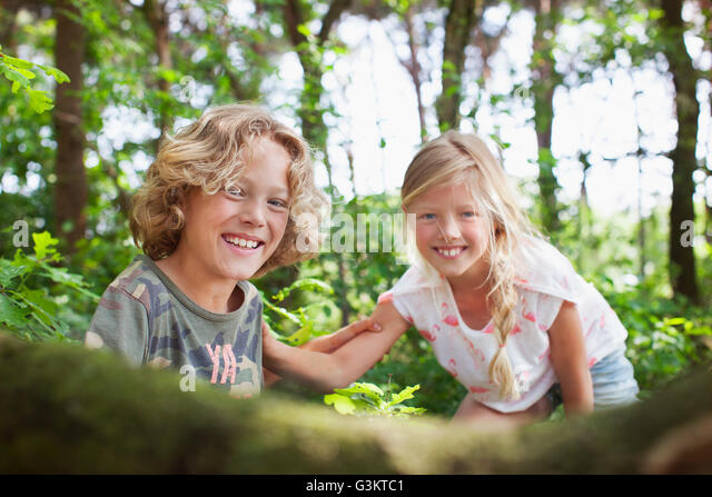 Boy and girl in forest looking at camera smiling - Stock Image