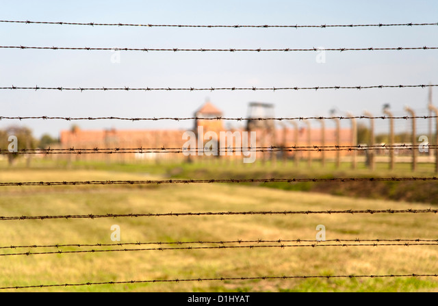 Barbed-wire fencing and buildings at the museum of the former Auschwitz II–Birkenau concentration camp in southern - Stock Image