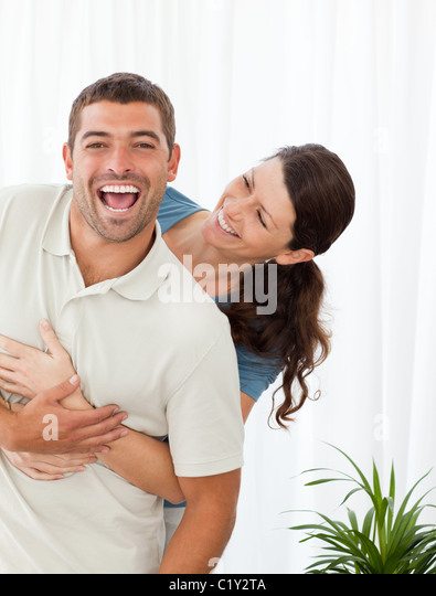 Joyful couple laughing together in the living-room - Stock Image