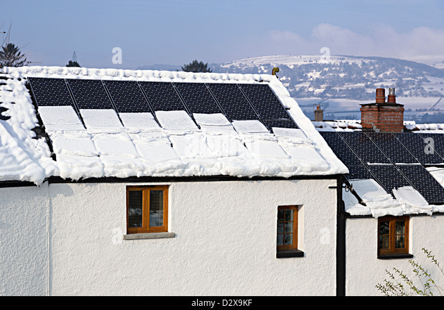 Snow sliding off solar pv panels and putting weight onto gutters of house, Llanfoist, Wales, UK - Stock Image