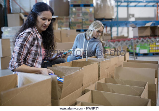 Female volunteers filling donation boxes in warehouse - Stock Image