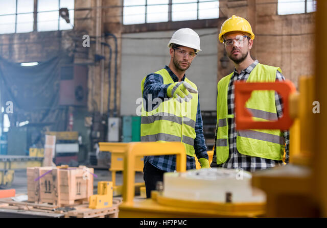 Steel workers talking and pointing in factory - Stock Image