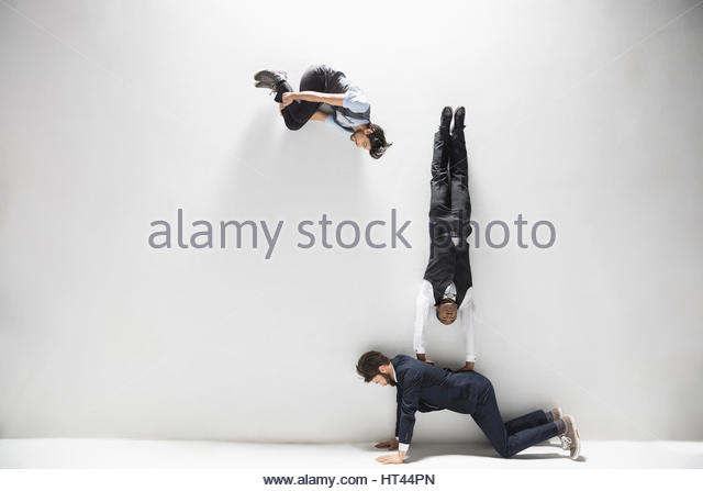 Business people balancing and flipping against white background - Stock-Bilder