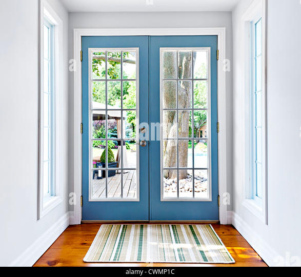 Double patio french doors with windows exiting to sunny backyard - Stock Image