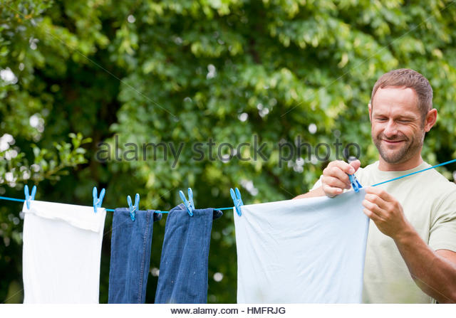 Man hanging laundry clothing on clothesline with clothespins in summer yard - Stock-Bilder