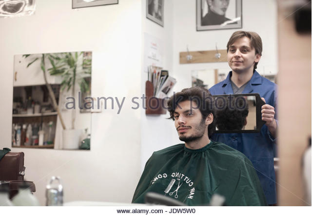 Hairdresser showing customer haircut in mirror - Stock-Bilder