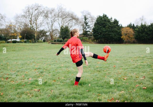 Teenage female soccer player practicing keepy uppy in park - Stock Image
