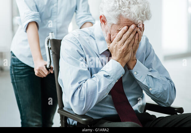 Sad depressed man in wheelchair with head in hands, a woman is taking care of him - Stock Image