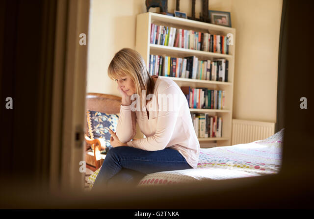 Depressed Mature Woman Sitting On Bed At Home - Stock Image