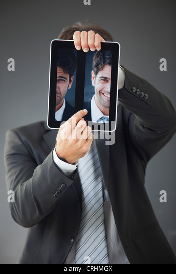 Man hiding behind images of himself frowning and smiling - Stock Image