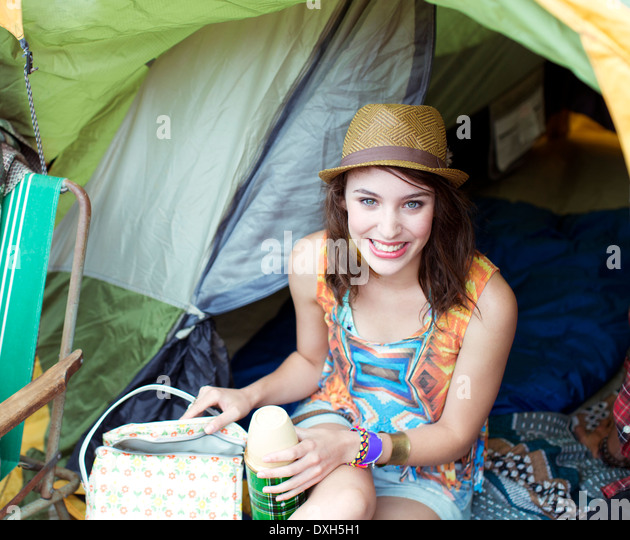 Portrait of smiling woman in tent at music festival - Stock-Bilder