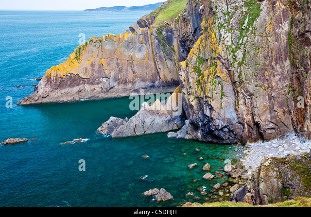 Rocky coastline and cliffs at Baggy Point a headland near Croyde, North Devon, England, UK. Morte Point in the distance, - Stock Image