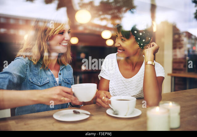 Two multi ethnic friends enjoying coffee together in a coffee shop viewed through glass with reflections as they - Stock Image