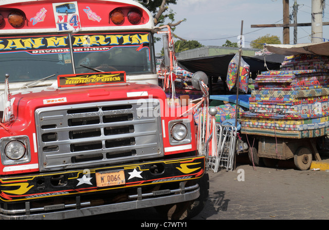 Nicaragua Managua Mercado Oriental flea market marketplace shopping stall public bus painted vehicle red painted - Stock Image