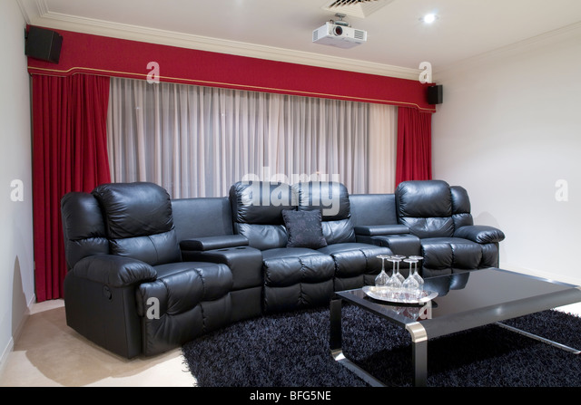 home theater room with black leather recliner chairs, red curtains, black rug and table with wine glasses - Stock-Bilder