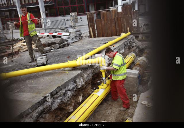 Workmen fitting new gas main pipes. - Stock-Bilder
